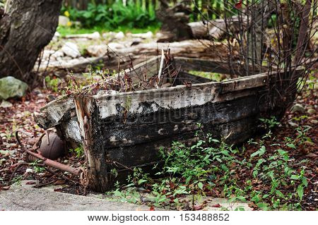 Last place of old broken boat in autumn garden.