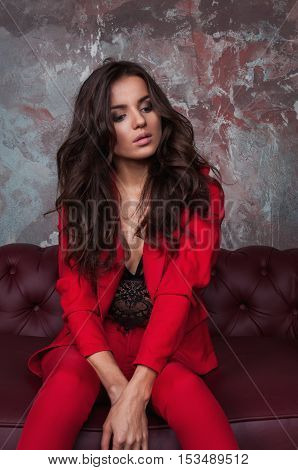 Portrait of a sexy young business lady in a red suit on a dark sofa