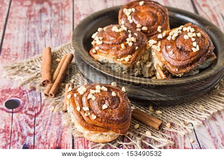 Homemade buns with marzipan and cinnamon in a wooden bowl on sackcloth on an old wooden table.