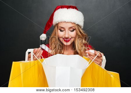 Cheerful beautiful young woman in santa claus costume looking inside shopping bag over black background
