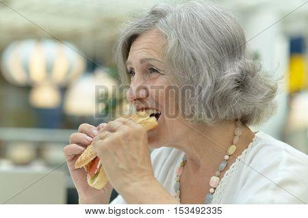 Portrait of happy elderly woman eating fast food