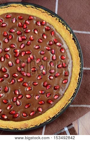 Homemade dessert chocolate tart with pomegranate arils