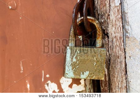 Close up old master key and rusty lock on the door