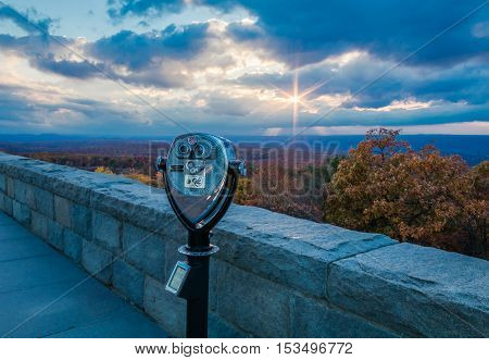 Binoculars point towards a majestic sunburst overlooking brilliant fall foliage at the top of New Jersey at High Point State Park