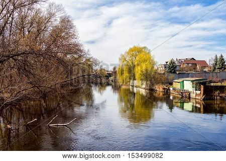 Springtime landscape - river with small village and forest on the banks, dry tree branches floating in a water with sky reflections