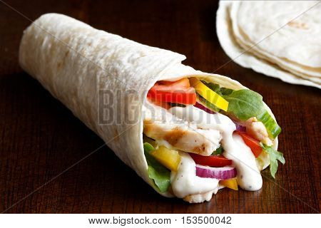 Grilled Chicken And Salad Tortilla Wrap With White Sauce Isolated On Dark Background. Next To Pile O