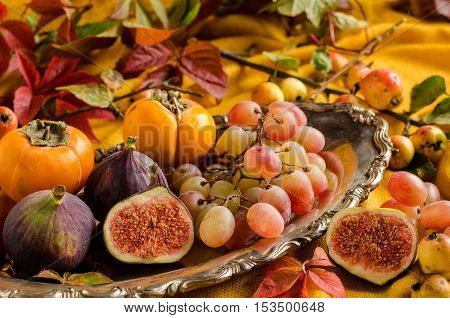 Persimmon figs grapes on a platter. Vintage silver dish. Fallen yellow and red leaves. Yellow background.