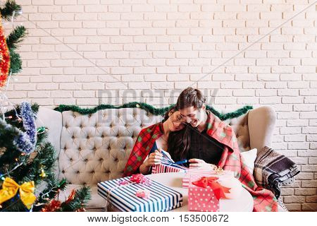 Happy couple sitting near Christmas tree, copy space. X-mas celebration, joy, coziness, love concept