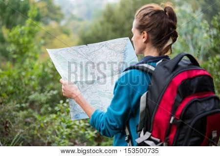 Rear view of female hiker looking at map in forest