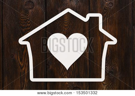 Paper house with heart inside. Love, relations, family concept. Dark wooden background. Abstract conceptual image
