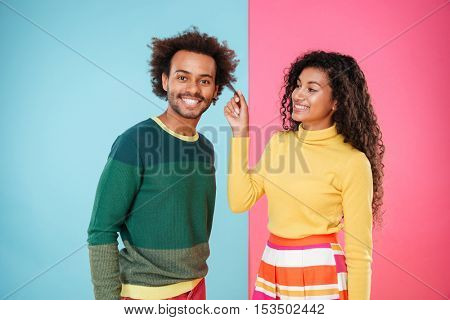 Cheerful african young couple having dun together over colorful background
