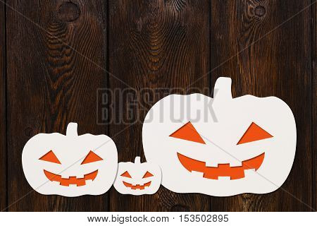 Halloween holiday. Three paper smiling Grand Pumpkins. Dark wooden background, copyspace. Abstract conceptual image
