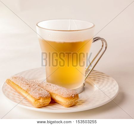 Close up on pair of delicious sponge biscuits and hot yellow tea on plate over bright table