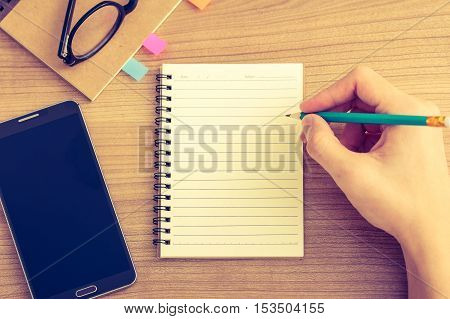 Top view right hand writing on blank notebook on wooded table with smartphone and glasses in vintage tone
