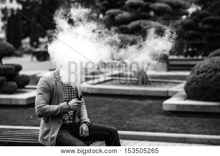 Men With Beard Vaping Electronic Cigarette Outdoor