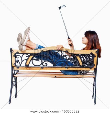 Back view of a woman to make a selfie stick portrait sitting on the bench. girl watching.  backside view of person. Isolated over white background. girl lying on a bench and photographed.