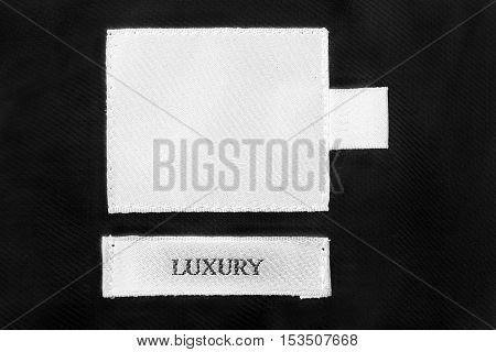 White clothes label lettered luxury on black cloth as a background