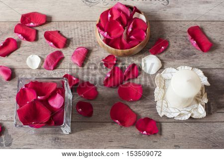 Glass Vase And Wood Bow Filled With Red Rose Petals, White Aromatic Vanilla Candle. Wooden Backgroun