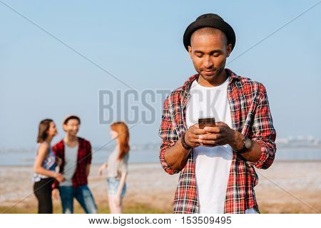 Pensive african young man in hat standing near his friends and using on mobile phone