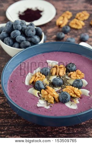 Acai berry smoothie bowl with blueberry, coconut, walnut and chia seeds