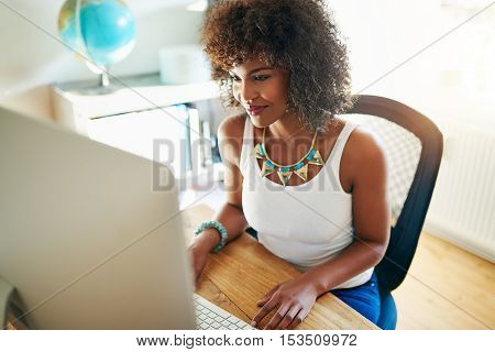 Pretty young woman working on a start up business from a bright airy office at home reading information on her desktop monitor