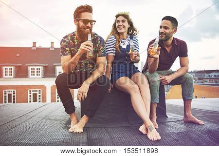 Happy group of three barefoot adults drinking beer on roof outdoors with copy space in sky