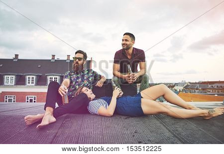Singing young woman laying in lap of bearded man near friend on roof in European city drinking bottles of beer