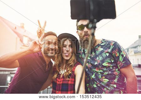 Man with beard and sunglasses makes bunny ears on friend as they take photo and make funny faces