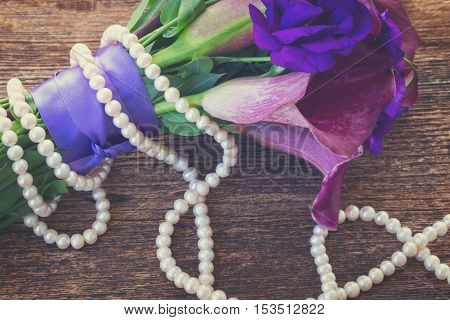 fresh calla lilly and eustoma flowers with pearls on wooden table, retro toned