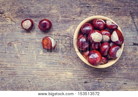 Fresh chestnuts in a bowl on an old wooden table. Group of chestnuts. Chestnuts - fruits horse chestnut - Aesculus hippocastanum. Dark background. Autumn background. Top view. Copy space.