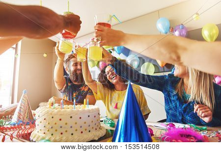 Group of young adult friends or coworkers toasting with yellow drinks over birthday cake