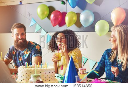 Smiling beautiful young woman sipping from yellow drink near birthday cake at party. Male and female friends sitting at left and right.