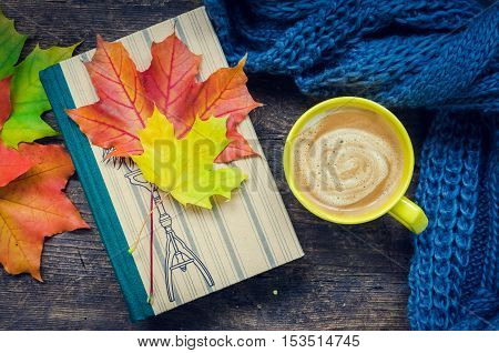Autumn still life - Warm knitted scarf, cup of coffee and a book on wooden table with fall maple leaves. Old book, knitted sweater with autumn leaves and coffee mug. Autumn cozy background. Top view.
