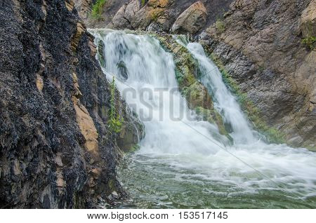 falling water in the morning mist. falling water in the dense morning fog. Water falling from a cliff. falling from a height of water. falling water in the fog. thick morning fog in the summer forest.
