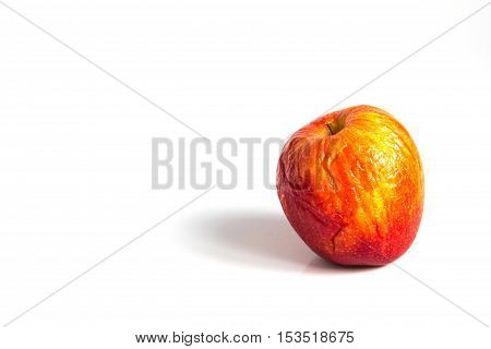 Wizen red apple placed on white background