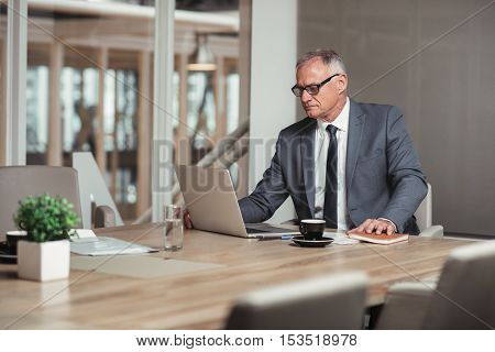 Confident mature businessman in a suit using a laptop while sitting at a table in an office boardroom