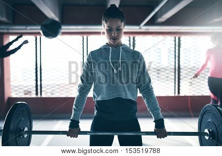 Fit healthy woman lifting a weight barbell exercising with group of people looking determined and focused