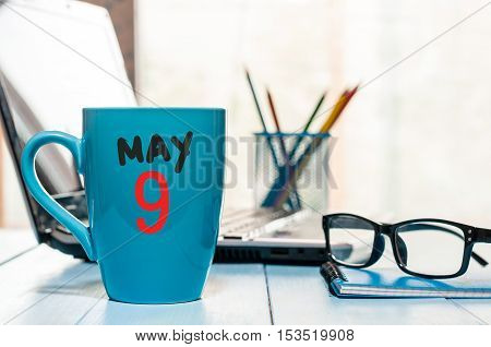May 9th. Day 9 of month, calendar on morning coffee cup, business office background, workplace with laptop and glasses. Spring time, empty space for text.