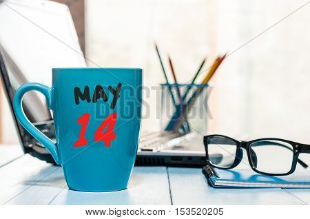 May 14th. Day 14 of month, calendar on morning coffee cup, business office background, workplace with laptop and glasses. Spring time, empty space for text.