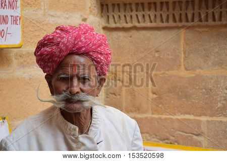 JAISALMER, RAJASTHAN, INDIA - FEBRUARY 10, 2016 - Portrait of an unidentified aged indian man with mustaches and traditional red turban