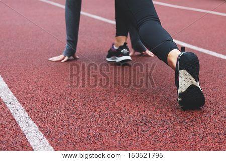 Female runner ready for running sprint. Woman in starting line runner pose for training in a park.