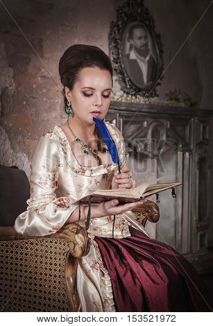 Beautiful woman in old historic medieval dress with diary
