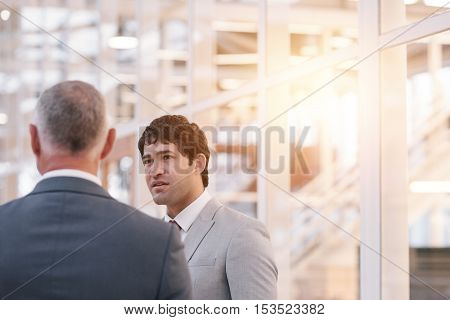 Focused young businessman talking to a mature manager while standing together in the lobby of a modern office building