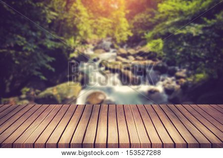 Waterfall On A Mountain Creek. In The Foreground A Wooden Planks.can Be Used For Montage Or Display