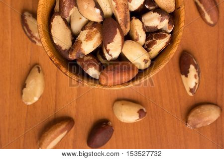 Brazilian Nuts into a bowl. Castanha do Para over a wooden table