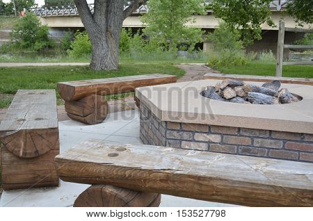 Log bench seats around a large outdoor fire pit for social gathering