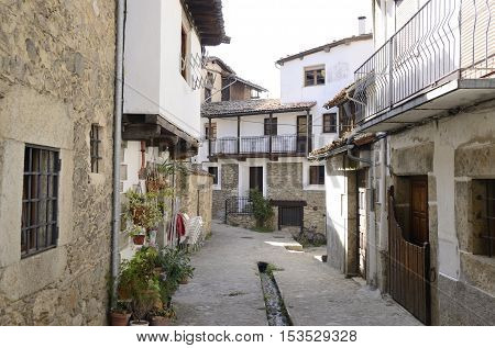 Small channel with clear water collected from the snowfields of the mountain at the floor of the street in Candelario a village of the province of Salamanca Spain.