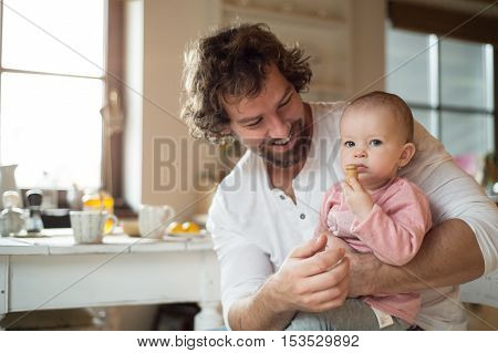 Young father at home holding his cute little daughter in his lap