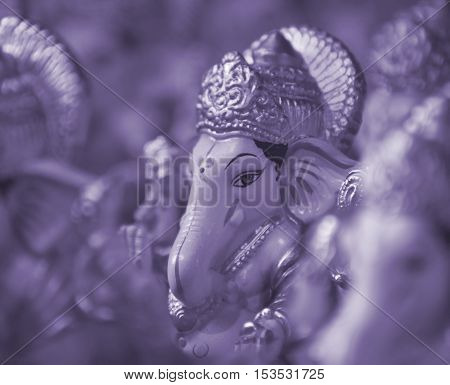 A background of a beautiful sculpted idol of lord Ganesha in violet filter.