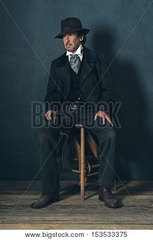 Vintage 1900 Western Mature Man With Revolver Sitting On Wooden Stool.
